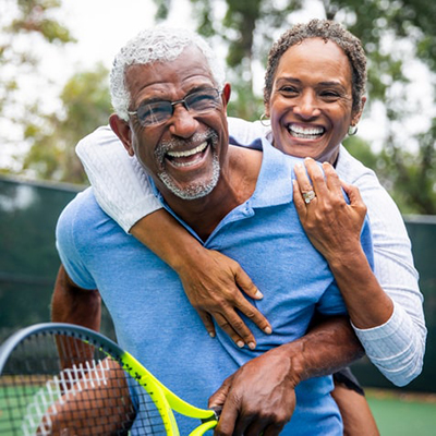 Older couple embracing and laughing on tennis court