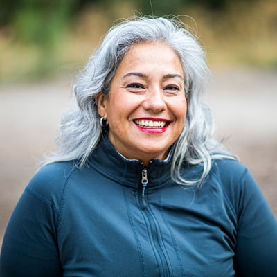 Middle aged woman with gray hair and beautiful teeth smiling