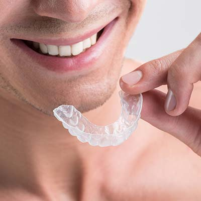 Man holding Invisalign clear aligners as he prepares to put them in his mouth.