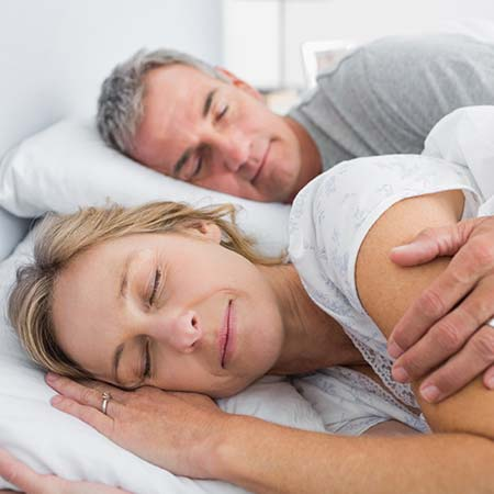 Husband and wife sleeping soundly in their bed after sleep medicine in Simpsonville, SC