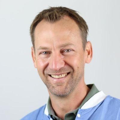 Dr. Brooks A. Godwin wearing blue scrubs smiling