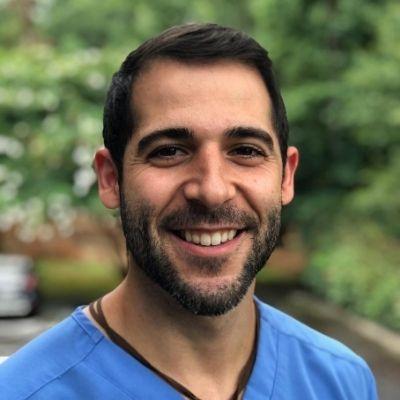 Simpsonville dentist, Dr. Shawn Boudreaux, in blue scrubs standing outside.